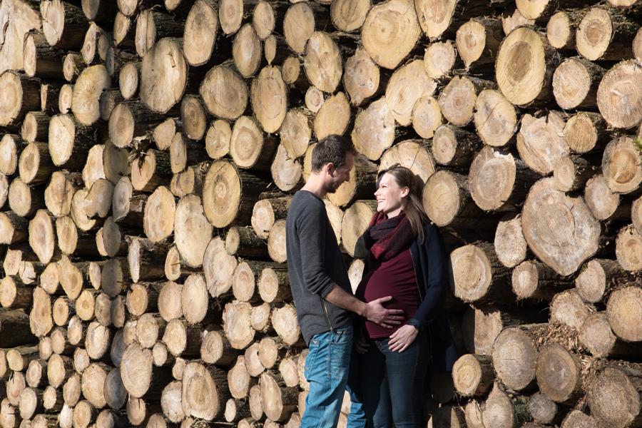 Als je durft ga dan mee op pad net als dit zwangere stel bij een stapel boomstammen in de Waarderhout. Lisa Muller Fotografie Heerhugowaard