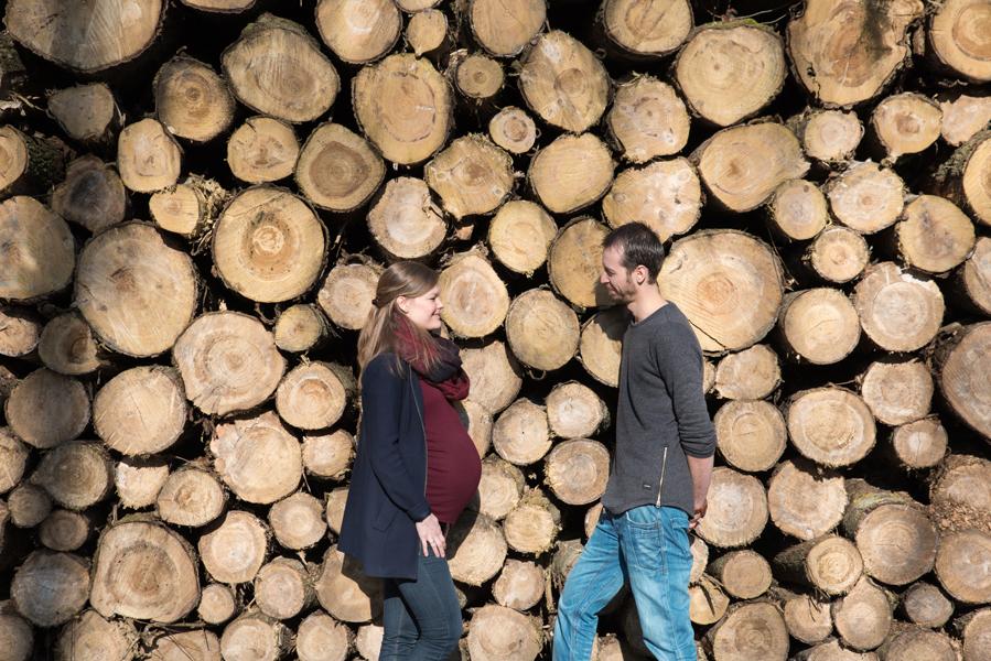 Zwangerschapsfotografie van een zwanger stel bij een stapel boomstammen. Bel Lisa Muller Fotografie +31 624809726 voor een mooie zwangerschapsreportage