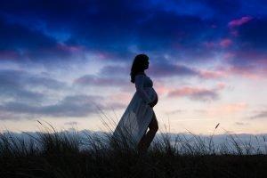 Een zwangere dame en een prachtige zonsondergang. Deze stijl foto