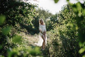 In een prachtige witte jurk in een groene omgeving staat deze vrouw die in verwachting is op de foto.