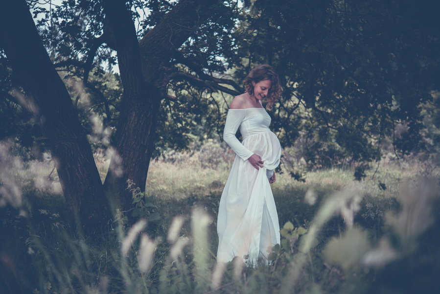 Zwangerschapsfotografie door Lisa Muller Fotografie. Deze foto is van een zwangere dame in een mooie witte jurk bij een oude boom.