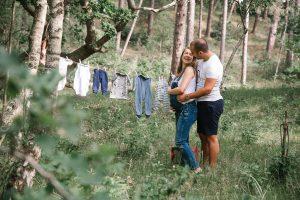 De babykleertjes worden opgehangen in het bos door een zwangere dame.