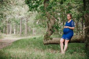 Een foto van een vrouw in een blauwe jurk. Zij doet een zwangerschapsshoot