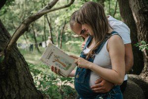 Foto van vader en moeder in spe lezend in boek tijdens zwangerschapsshoot