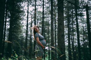 Een zwangere dame in een mooie jurk in een dennenbos. Natuurlijk wil jij ook zo