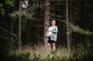 Mooie zwangere dame in een dennenbos, ze draagt een blauw vest
